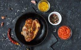 Sappig varkensvleeslapje vlees met kruiden op pan op donkere steenachtergrond bovenkant royalty-vrije stock fotografie