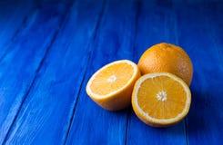 Sappige gehele sinaasappel en de twee helften op de donkerblauwe houten achtergrond Stock Afbeelding