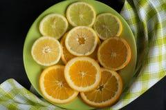 Sappige, gesneden citrusvruchtencitroen, oranje achtergrond op plaat dichtbij groen servet Hoogste mening Royalty-vrije Stock Afbeeldingen