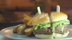 Sappige hamburgerhamburger op een sesambroodje met bacon en kaas en gediend met knapperige frieten, verkeerd op de lijst stock footage