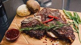 Sappige het lapje vleesfilet van het rundvleesvlees op houten plaat met peper, knoflook en rozemarijn 4K in langzame motie stock videobeelden