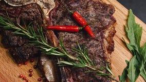 Sappige het lapje vleesfilet van het rundvleesvlees op houten plaat met peper, knoflook en rozemarijn 4K in langzame motie stock video
