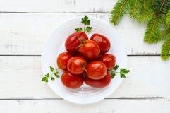 Sappige kruidige gemarineerde tomaten op een witte plaat Stock Foto