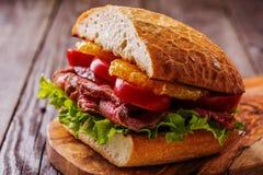 Sappige lapje vleessandwich met groenten en plakken van sinaasappel Royalty-vrije Stock Fotografie