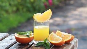 Sappige plakken van rijp sinaasappelen en jus d'orange aan een glas stock video