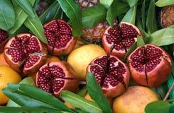 Sappige rijpe granaatappels op het gebladerte Stock Afbeelding