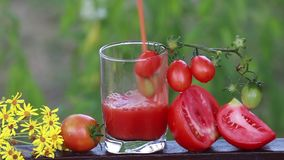 Sappige rijpe rode tomaten en vers tomatesap in een glas stock video