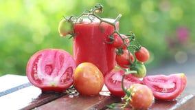 Sappige rijpe rode tomaten en vers tomatesap in een glas stock footage