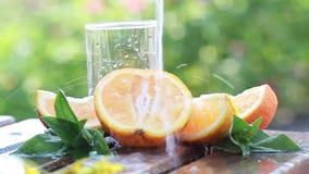 Sappige rijpe sinaasappelen en een stroom van schoon water stock video