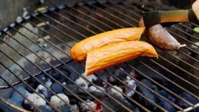 Sappige worst bij de hete grill tijdens de zomerbarbecue in langzame motie stock footage