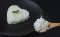 Saque do arroz do cozinheiro com forma do coração no prato preto com fumo imagem de stock royalty free