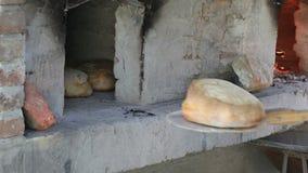 Saque el pan con la pala de madera del horno almacen de video