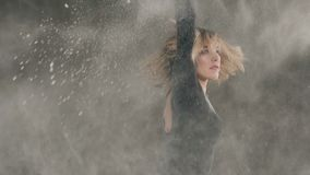 Saque el polvo, el polvo blanco, muchacha que el bailarín en ropa negra hace círculos alrededor de sí misma en dentro en fondo gr almacen de video