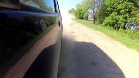 Saque el polvo de levantamiento del automóvil de las ruedas del automóvil que conduce en el camino rural de la grava almacen de video