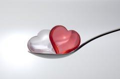 Saque las pequeñas misceláneas de la dimensión de una variable con pala del corazón con una cuchara Fotografía de archivo