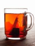 Saquinho de chá na caneca de vidro na tabela de madeira Fotos de Stock Royalty Free