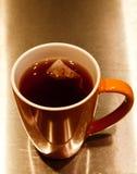 Saquinho de chá que embebe no copo cerâmico alaranjado Fotos de Stock Royalty Free