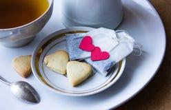 Saquinhos de chá com coração cookies do café da manhã sob a forma dos corações Imagens de Stock