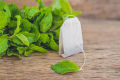Saquinhos de chá no fundo de madeira com melissa fresco, hortelã Chá com conceito da hortelã Imagem de Stock Royalty Free