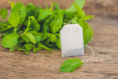 Saquinhos de chá no fundo de madeira com melissa fresco, hortelã Chá com conceito da hortelã Fotos de Stock