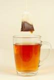 Saquinhos de chá sobre o vidro com chá forte fresco Fotografia de Stock Royalty Free