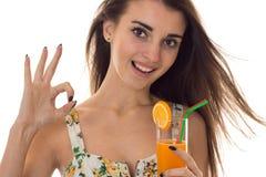 sarafan的显示年轻愉快的深色的女孩与花卉样式喝橙色鸡尾酒微笑在照相机和好 库存照片