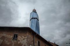 SARAJEVO, BOSNIA Y HERCEGOVINA - 16 DE ABRIL DE 2017: Avaz Twist Tower en la lluvia, con una casa vieja destruida en frente Fotos de archivo