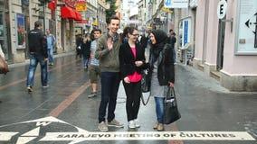 SARAJEVO BOSNIEN - MARS 2014: Lokaler som framme poserar av det sarajevo för ½ för ¿ för ï för gatatecken mötet av culturesï¿ ½ p stock video