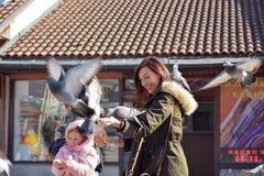 Sarajevo, Europa 09 02 2018, quadrado de cidade com mãe e pombos de alimentação da filha Fotos de Stock