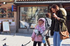 Sarajevo, Europe 09.02.2018, city square with mother and daughter feeding pigeons Stock Photos