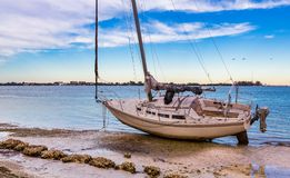 Sarasota, FL am 20. Januar - auf den Strand gesetztes Segelboot nach einem seltenen Tornado schlug Sarasota Ende Januar 2016 Stockfotos