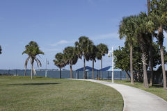 Sarasota, Florida Park. Curved sidewalk, palm trees and grass leading to a Gulf coast water view from Whitaker Gateway Park in north Sarasota, FL on a sunny Stock Photo