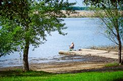An elderly man is fishing on the banks of the Volga River royalty free stock photography