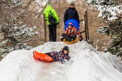 Saratov / Russia - March 8, 2018: Children ride with an ice slide. Winter vacation. Outdoor activity. Winter day in the city Park.  Stock Images