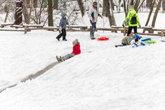 Saratov / Russia - March 8, 2018: Children ride with an ice slide. Winter vacation. Outdoor activity. Winter day in the city Park.  Royalty Free Stock Images