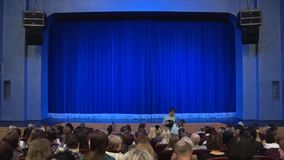 People in the auditorium of the theater before the performance or in the intermission. Blue curtain on stage. Shooting from behind