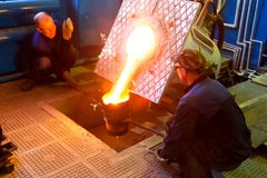 Furnace for metal remelting. Pouring metal from the furnace by workers. royalty free stock images
