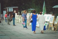 People walk in the park at the celebration of the city`s day and look at the exhibition of pa royalty free stock photo