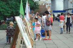 People walk in the park at the celebration of the city`s day and look at the exhibition of pa vector illustration
