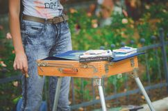 A pupil of an art school draws in a park. sketchbox with paints, close-up. stock images