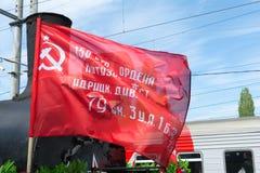 SARATOW, RUSSLAND - 6. MAI 2017: Fragment einer alten Militärlokomotive mit einer Abteilung der roten Fahne Stockbild