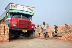 SARBERIA INDIEN, JANUARI 16: Tegelstenfältarbetare som bär färdig fullföljandetegelsten från brännugnen, och laddat det på en las Royaltyfria Bilder