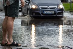 Man looking at the car on a flooded street Stock Images