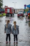 Two sisters looking at an aftermath of torrential rain Stock Photo