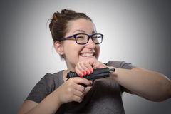 Sarcastic girl with a gun, grimace portrait. On dark background Royalty Free Stock Photo