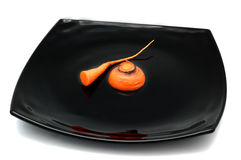 Sarcastic healthy diet concept. Irony healthy diet concept - bit of carrot on black plate Royalty Free Stock Photo