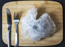 Close up view on a crumpled plastic bag as a dish plate, image topic is for environment plastic polution stock images