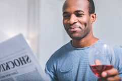 Sarcastic man reading a newspaper. Funny news. Sarcastic smiling man reading a newspaper while drinking wine Stock Photography