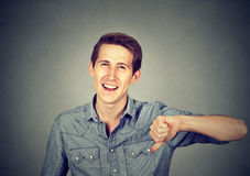 Sarcastic man showing thumbs down, happy someone lost. Closeup portrait sarcastic young man showing thumbs down sign hand gesture, happy someone lost  on gray Royalty Free Stock Photography