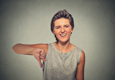 Sarcastic young woman showing thumbs down sign hand gesture. Closeup portrait sarcastic young woman showing thumbs down sign hand gesture, happy someone made Stock Images
